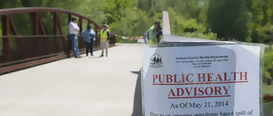 A notice of a public health advisory is posted near the Grand River in Lions Park in Jackson on Thursday , May 22, 2014.. Hundreds of gallons have spilled into the river. The EPA, DEQ and city officials are on scene supervising the cleanup. (J. Scott Park | MLive.com)