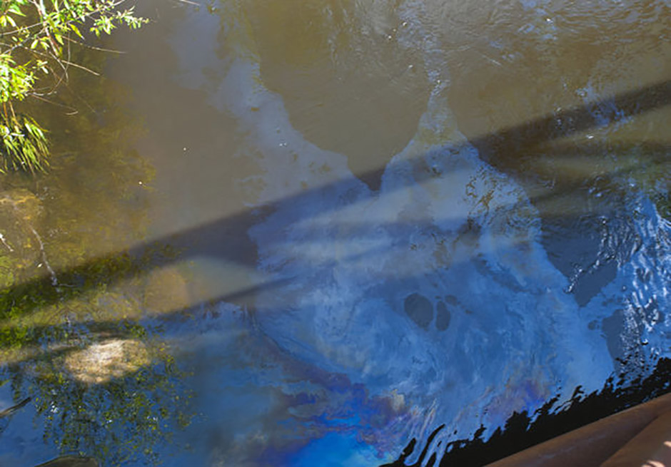 Oil can be seen on the surface of the Grand River in Lions Park in Jackson near an oil boom on Thursday , May 22, 2014.. Hundreds of gallons have spilled into the river. The EPA, DEQ and city officials are on scene supervising the cleanup. (J. Scott Park | MLive.com)